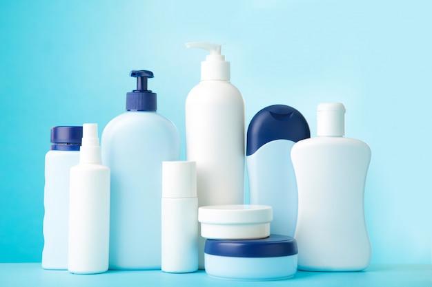 Verschillende cosmetische flessen op blauwe achtergrond. bovenaanzicht