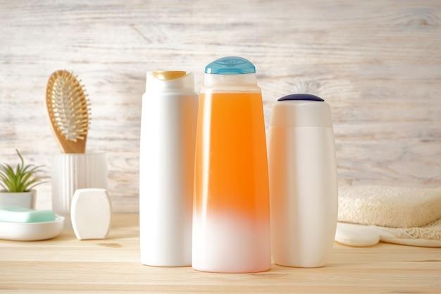 Verschillende cosmetische flessen op houten achtergrond. zeep- en shampooflessen, haarborstel