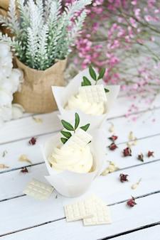 Verschillende cupcakes en muffins met witte botercrème op een witte houten tafel.
