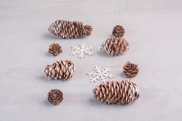 Verschillende dennenappels en sneeuwvlokken op witte tafel.