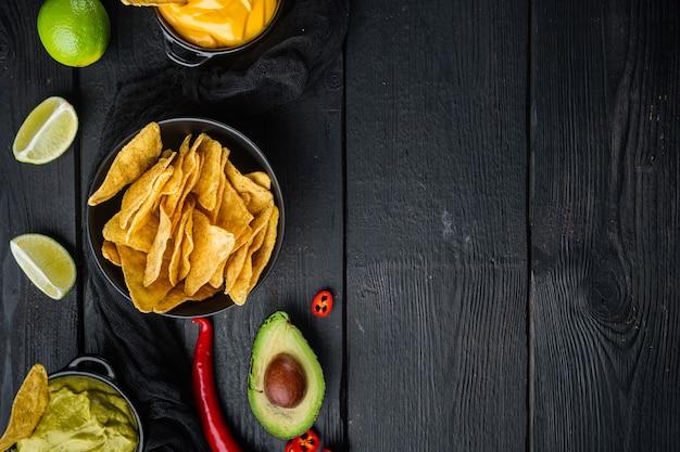 Verschillende dipsauzen en sauzen voor nacho's, op zwarte houten tafel, bovenaanzicht of plat
