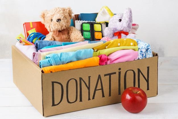 Verschillende donaties in een doos - kleding, briefpapier en speelgoed. kleding voor kinderen en tieners. voorbereiding op school.