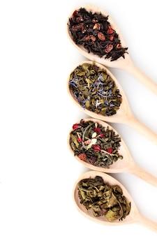 Verschillende droge groene en zwarte thee in houten lepels die op wit worden geïsoleerd