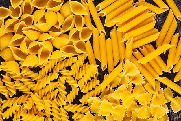 Verschillende droge pasta op een houten achtergrond. bovenaanzicht