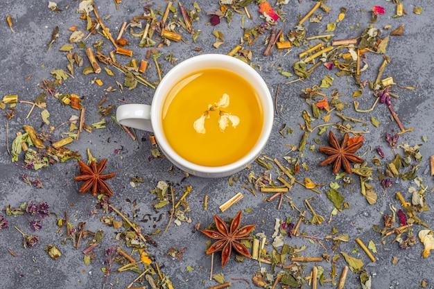 Verschillende droge theeblaadjes en kopje groene thee