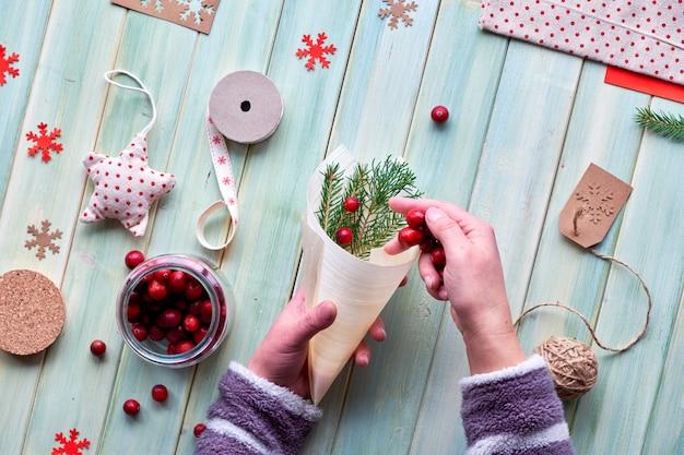 Verschillende eco- of kerstversieringen voor kerstmis of nieuwjaar, ambachtelijke papieren pakketten en herbruikbare geschenken of geen afval. plat op houten planken, cranberry in multiplex kegel met groene bladeren.