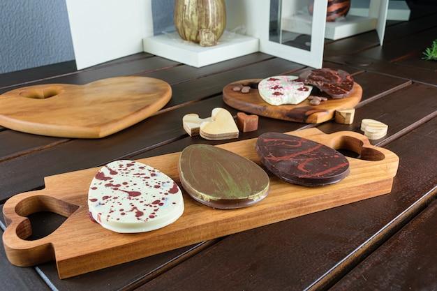 Verschillende eivormige chocolaatjes op een hout. op de achtergrond traditionele paaseieren in dozen.