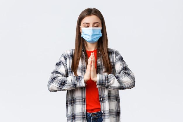 Verschillende emoties, covid-19 pandemie, coronavirus zelfquarantaine en sociaal afstandsconcept. geduldige en rustige jonge vrouw met medisch masker, biddend, mediteren met de handpalmen tegen elkaar en gesloten ogen