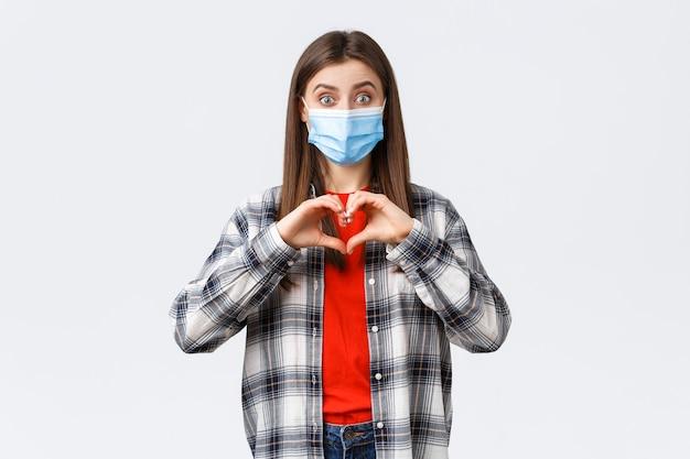 Verschillende emoties, covid-19 pandemie, coronavirus zelfquarantaine en sociaal afstandsconcept. opgewonden jonge vrouw met medisch masker die bekentenis aflegt, hartteken toont als iemand, medeleven betuigt.