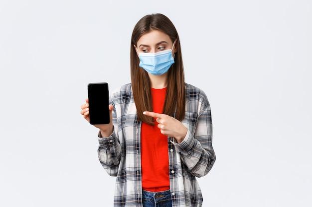 Verschillende emoties, covid-19, sociale afstand en technologieconcept. aantrekkelijke 20-er jaren vrouw met medisch masker, wijzende vinger naar mobiele telefoon, advies download app of game, filters voor foto's
