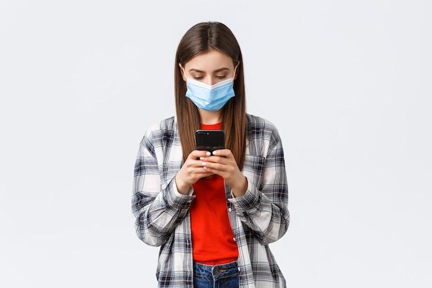 Verschillende emoties, covid-19, sociale afstand en technologieconcept. aantrekkelijke jonge vrouw met medisch masker sms-bericht, kijkend naar het scherm van de mobiele telefoon druk, thuiswerkend
