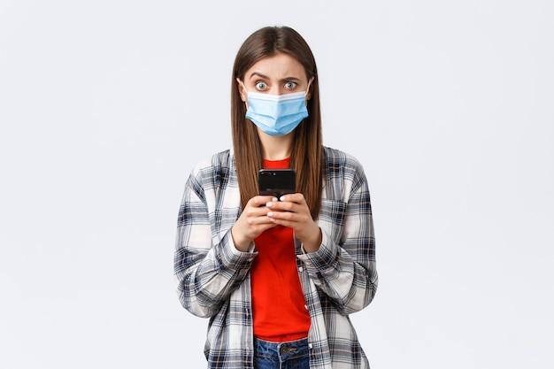 Verschillende emoties, covid-19, sociale afstand en technologieconcept. verbaasde en verwarde jonge vrouw met medisch masker reageert op vreemd bericht, houdt mobiele telefoon vast, kijkt camera onzeker.