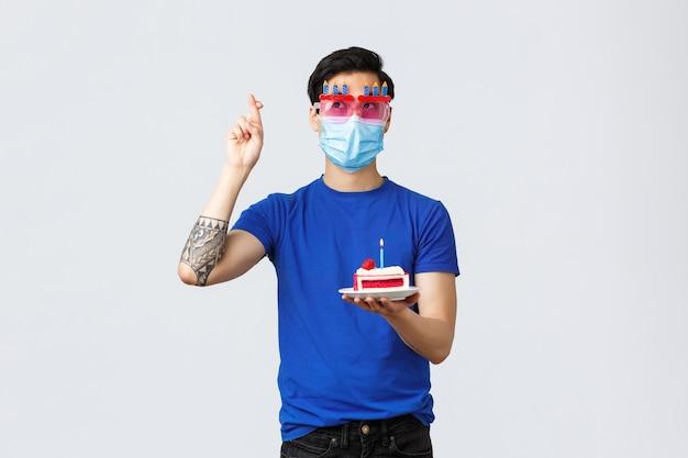 Verschillende emoties, sociale afstand, zelfquarantaine op covid-19 en lifestyle-concept. jonge, schattige aziatische man met een grappige bril, medisch masker, verjaardagstaart met gekruiste vingers en wensen