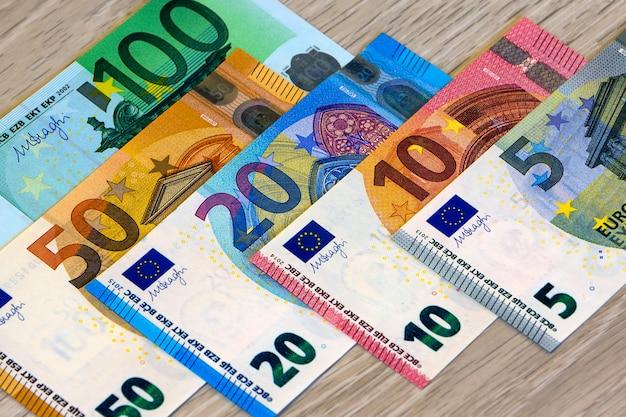 Verschillende euro geldbankbiljetten op houten achtergrond