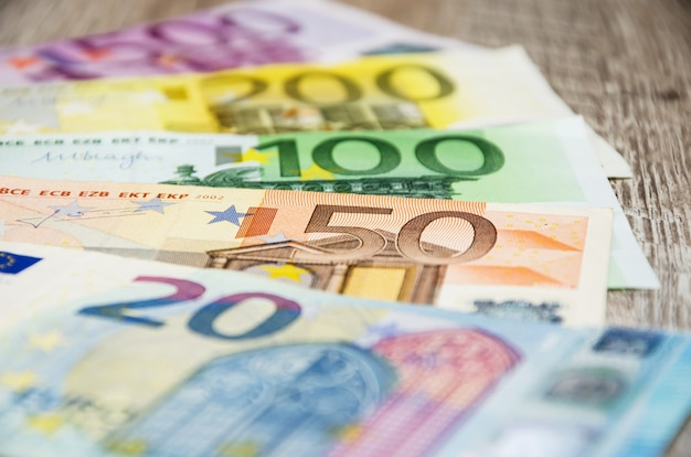 Verschillende eurobiljetten op een houten tafel