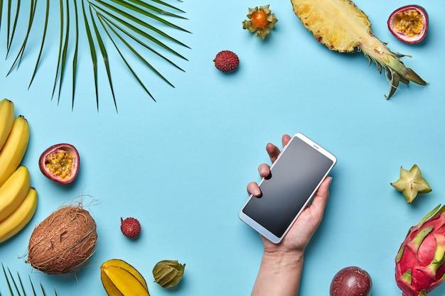 Verschillende exotische vruchten en een palmblad met mobiele telefoon