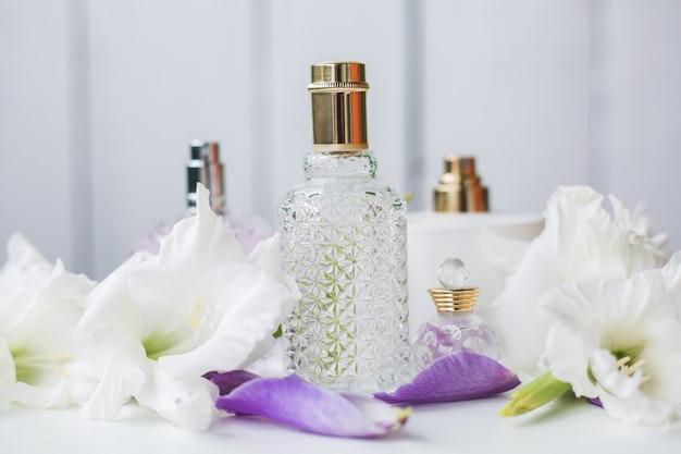 Verschillende flessen parfum met witte bloemen