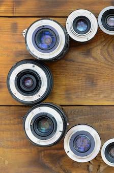 Verschillende fotografische lenzen liggen op een bruine houten achtergrond. ruimte voor tekst