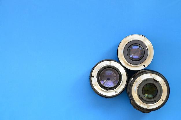 Verschillende fotografische lenzen liggen op een helderblauwe achtergrond. ruimte voor tekst
