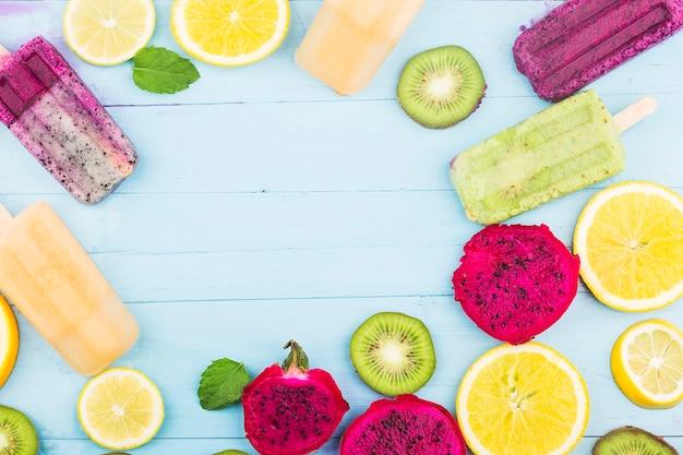 Verschillende fruitijslollys worden op de blauwe houten plankachtergrond geplaatst, kiwi-ijslollys, oranje ijslollys, drakenfruitijslollys, meloenijslolly