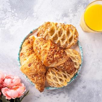 Verschillende gebakken broodjes op een bord met sinaasappelsap. ochtend ontbijt concept. bovenaanzicht