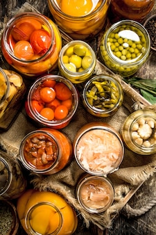 Verschillende geconserveerde groenten van groenten en champignons in glazen potten. op een houten tafel.
