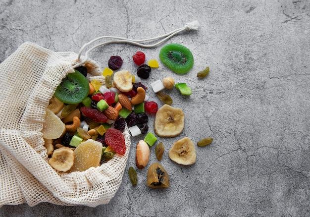Verschillende gedroogde vruchten en noten in een eco-zak op een grijze betonnen ondergrond