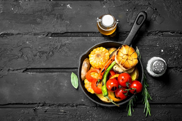 Verschillende gegrilde groenten in een pan op donkere rustieke tafel.