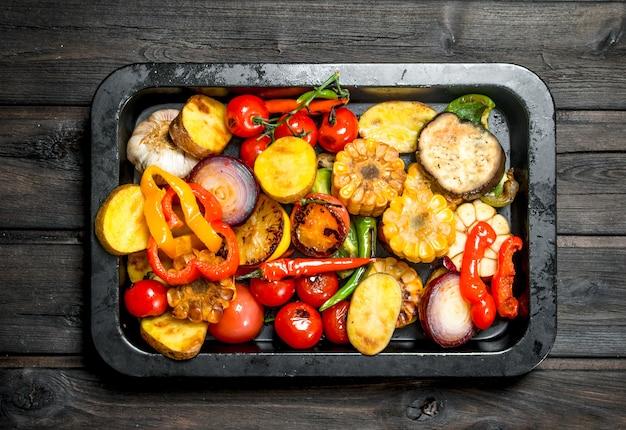 Verschillende gegrilde groenten met kruiden en specerijen op houten tafel.