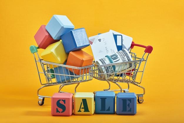 Verschillende gekleurde blokken met de formuleringen verkoop, geïsoleerd tegen geel