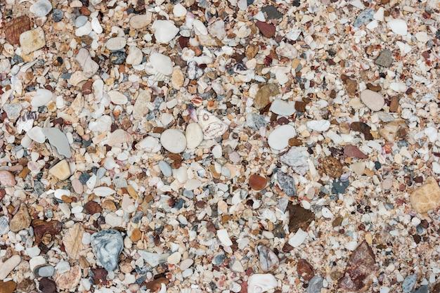Verschillende gekleurde kiezels of strandstenen op een strand voor aardachtergrond.