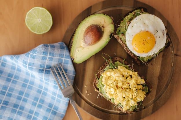 Verschillende gekookt ei op avocado sandwich met volkoren brood op een houten bord. bovenaanzicht