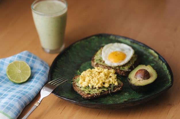 Verschillende gekookt ei op avocado sandwich met volkoren brood op een houten bord. smoothie met spinazie.