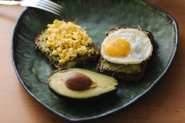 Verschillende gekookt ei op avocado sandwich met volkoren brood op groene plaat. smoothie met spinazie.