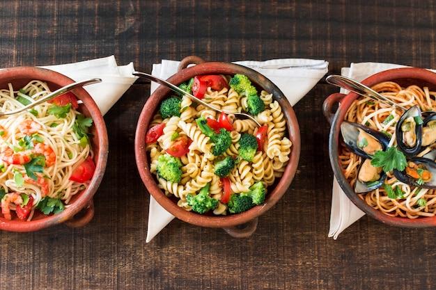 Verschillende gekookte pasta in het aardewerk met gevouwen servet op houten tafel