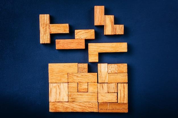 Verschillende geometrische vormen houten blokken schikken in solide figuur op een donkere achtergrond.
