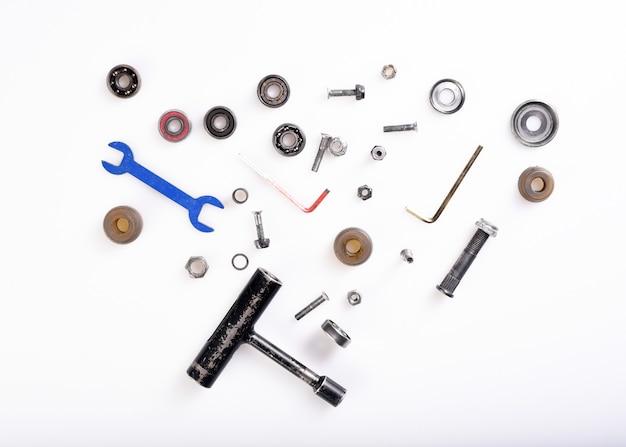 Verschillende gereedschappen, bouten, lagers op wit oppervlak.