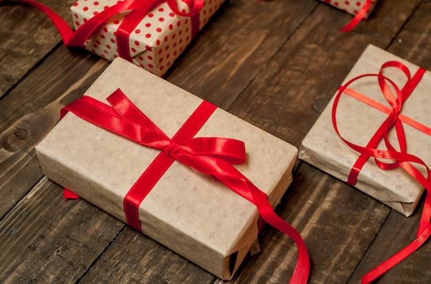 Verschillende geschenken met rood lint op hout achtergrond