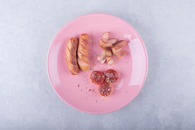 Verschillende gevormde gebakken worstjes op roze plaat.