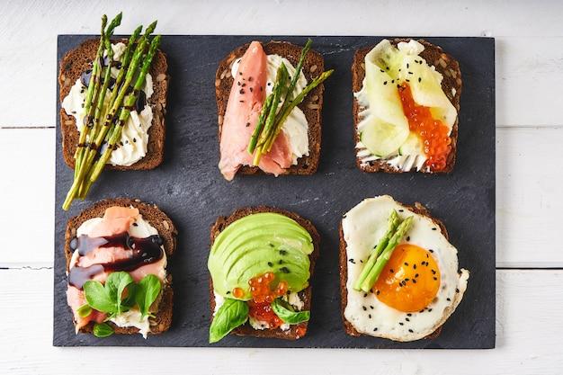 Verschillende gezonde sandwiches met verschillende soorten beleg. vis, kaviaar, avocado, asperges, komkommer, kruiden, sesamzaadjes, glutenvrij brood geserveerd op een donkere schaal