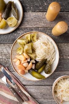 Verschillende gistingen op een bord. gefermenteerde kool, komkommers, tomaten en knoflook. bovenaanzicht