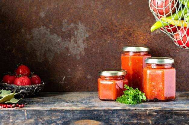Verschillende glazen potten met zelfgemaakte tomatensaus op een houten zijtafel. kopieer ruimte