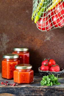 Verschillende glazen potten met zelfgemaakte tomatensaus op een houten zijtafel