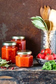 Verschillende glazen potten met zelfgemaakte tomatensaus op een houten zijtafel.