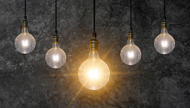 Verschillende gloeilamp idee veel lampen zijn gerangschikt in een rij en een van hen is verlicht. concept idee