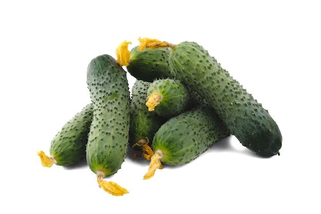 Verschillende groene komkommers met verdorde gele bloemen worden in willekeurige volgorde gestapeld en geïsoleerd op een schone witte achtergrond met zachte schaduwen.