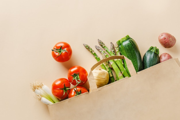Verschillende groenten in papieren zak op beige