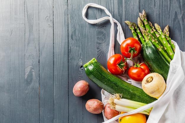Verschillende groenten in textielzak op grijze copyspace