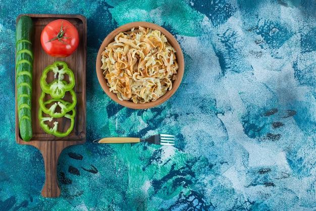 Verschillende groenten op een bord naast een vork en een kom noedels op de blauwe tafel.