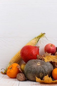 Verschillende groenten, pompoenen, appels, peren, noten, maïs, tomaten en droge bladeren op witte houten achtergrond. herfstoogst, copyspace.